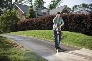 Man powerwashing driveway.