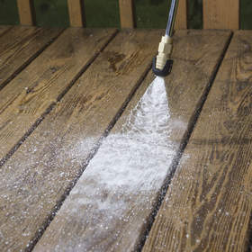 Powerwashing a wooden deck.