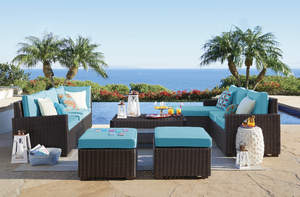 Beautiful outdoor furniture overlooking a pool and ocean.