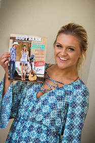 Kelsea Ballerini with the latest Boot Barn catalog featuring her as the face of the Shyanne brand.