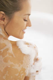 Woman soaping her shoulder in the shower.