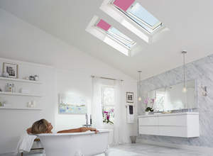 Woman soaking in a tub under Velux skylights.