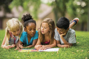 Children  grouped together on the grass reading a book.