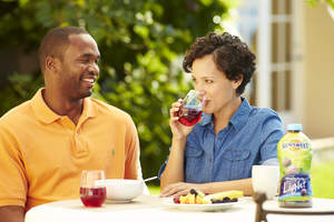 Man and woman drinking juice at a table.