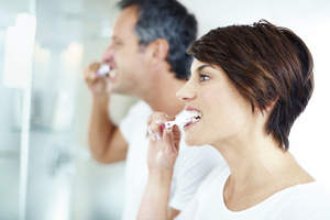 Man and woman brushing their teeth.
