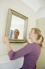 Woman hanging up mirror on wall.
