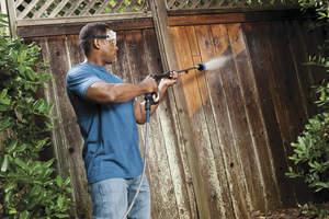 man power washing a fence