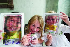 3 kids showcasing their work
