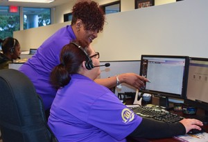 Scheduling Center Manager Delores White, standing, reviews a screen on the computerized Customer Wizard system with team member Levy Muniz.