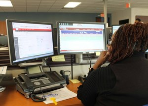 A Peoples Natural Gas worker in the Pittsburgh Dispatch Center opens a callout in the ARCOS solution (screen displayed at left). [Photo by Peoples Natural Gas].