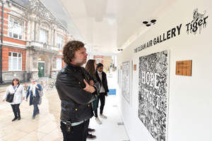 Visitors look at artworks inside the Tiger Beer 'Clean Air Gallery' in Brixton, the works were created using Air-Ink™, the first ink to be made from captured air pollution before it enters the atmosphere. London. PRESS ASSOCIATION Photo. Picture date: Monday March 27, 2017. Photo credit should read: Matt Crossick/PA Wire