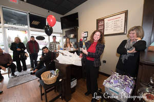 Susan Longworth shows her delight as she holds up the gift of rooster wind chimes from the Huntersville Chamber of Commerce