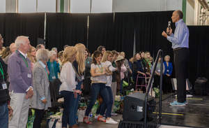 """Dr. Joseph Mercola gets crowd on their feet to exercise during his presentation, """"Fat for Fuel."""" Photo credit: Thomas Mizzoni"""
